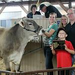 Michaela Price, of Wellington, left, stands with her reserve champion dairy steer and buyer, Ben Fligner, of Fligner's Market during the 2014 Lorain County Junior Fair Livestock Sale Saturda …
