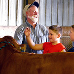 Brian Duplaga, of Grafton and owner of Duplaga Limousin Farms, teaches Cody Bolyard, 8, and his brother Zachary, 8, of LaGrange, about the different types of cows at Duplaga Limousin Farms.  …