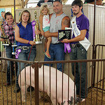 Delany Adams, of Spencer, center, stands with her grand champion market hog and buyer Denes Concrete after the hog was sold for $12/lb. ANNA NORRIS/CHRONICLE