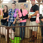 Dylan Minek, left center, stands with his reserve champion hog and buyers, Lighthouse Insurance, after the hog sold for $10/lb. ANNA NORRIS/CHRONICLE