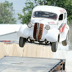 A 1937 Dodge Sedan jumps through the air between two sets of ramps during the Black Cat Hell Drivers stunt show Sunday afternoon at the Lorain County Fair in Wellington. ANNA NORRIS/CHRONICL …