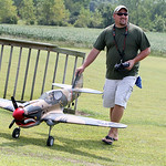 Brian Dee, of Vermilion, walks his radio controlled Top Flight p-40 Warhawk off the runway after flying it during the Lorain County Radio Control Club's annual Model Mania airshow in Elyria  …