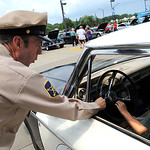 Deputy Barney Fife, played by Todd Beckett of Massillon, lets Abe Mastellone, of Amherst, try out the Ford patrol car's siren, at the Nick Abraham Elyria Ford 6th Annual Mustang and Ford Sho …