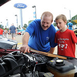 David Mease, and son Briar, 7, of Elyria, look under the hood of a 2006 Ford Mustang GT at the  Nick Abraham Elyria Ford 6th Annual Mustang and Ford Show, co-hosted by North Coast Mustang Cl …
