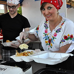 D.J. Forbush of Elyria, left, and Lisa Cuevas of Sheffield serve food at the Hungarian booth Saturday afternoon at Lorain International Festival. Cuevas said she was dressed up because she w …