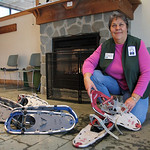 Volunteer MaryJo Slobuda shows some of the snow shoes available for rental at Sandy Ridge Reservation – Johnson Wetland Center. photo by Ray Riedel