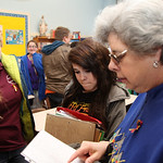 Eighth grade teacher Anna Schultz answers questions from her returning students Chloe Mieras, left,  (age 14) and Mariah Gonzalez, center, (age 14 ) as they move back into their classroom at …