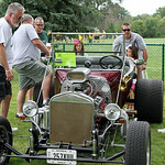 People look over Jim Calhoun's 1923 Ford T-bucket car in the St. Jude's car show during the annual parish festival Sunday afternoon in Elyria. ANNA NORRIS/CHRONICLE