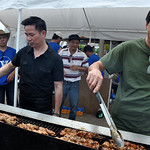 Don Vu of North Olmsted, left, and Van Tran of Berea cook chicken kebabs Sunday afternoon at the Vietnamese booth at Lorain International Festival. They represent St. Boniface Church on the  …