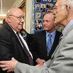 Rev. Ray Carpenter, left, greets John Riffle, on right, and Steve Morton, at a retirement party after 44 years at Faith Baptist Church in North Ridgeville on Mar. 9.