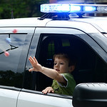 Carter Barrett, 5, throws candy to parade watchers from a Wellington Police cruiser during the annual Cheese Heritage Festival Parade on Saturday. KRISTIN BAUER | CHRONICLE