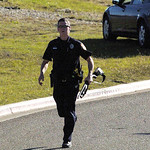 A member of the Fort Hood police department rushes down the street away from the Soldier readiness Center at Fort Hood following a mass shooting where Maj.Nidal Malik Hassan  shot and killed …