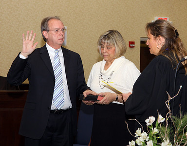 29dec09 bishop--- A full house at the Elyria Council Chambers as Gary Bennett was sworn in as a new Elyria Municipal Court Judge. He is being sworn in by Judge Donna Carr, Ninth District Court of Appeals. Holding the bible is Bennett's wife Marjory Bennett