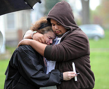 "Vicki Moore, ex-wife of homicide victim Lamar ""Mark"" Taylor, and his stepson Joe Lane, at a remembrance and prayer vigil for Taylor on E. 34th St. in Lorain,  on Apr. 14.  Over 50 people attended the vigil by Interfaith Ministries, in conjunction with family, friends and community leaders.   He was found beaten to death in a yard at 1964 E. 34th St.    Steve Manheim"