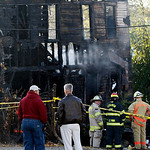Officials talk near a fire that occurred in the overnight hours and killed three people in Lebanon, Ohio Monday, Oct. 19, 2009. Three adults died in the early morning blaze that engulfed a c …