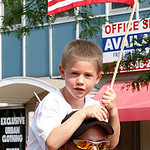 Little boy with flag Hunter Wilson being carried in the Elyria Parade by his father Tom Wilson.  Photo by Tom Mahl