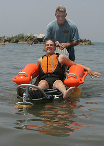 29JUN12   Samantha Taylor enjoys the special beach equipment --the Mobi Chair--a type of amphibious beach wheelchair--that's available at Lakeview Park.   Her dad Aaron is behind her.      Photo  by Chuck Humel