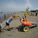 29JUN12   Samantha Taylor with a gleeful scream of delight– checks out the special beach equipment –the Mobi Chair–a type of amphibious beach wheelchair–that's available at Lakeview Park …