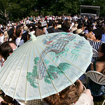 At 9 a.m. the heat was building, and, within the hour, the graduates took to their chairs, including Ellie Philips of New York city who used a parasol to shield herself from the record expec …