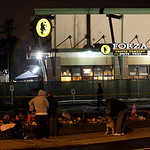Pedestrians view a growing display of flowers, candles, and messages of sympathy, in front of the Forza Coffee Company in Parkland, Wash., Monday, Nov. 30, 2009, where four Lakewood Police O …