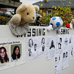 A board with flyers for missing persons is hung on a frnce across from the home of Anthony Sowell in Cleveland Thursday, Nov. 5, 2009. The remains of 11 women were found in Sowell's home. (A …