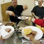 St Mary's held an Easter Dinner after Masses at the Newton Commons on St. Mary Way. Hall worker Dean DeMarco, left, and Ray Riedel fill the plates of servers who took the meals to the people …