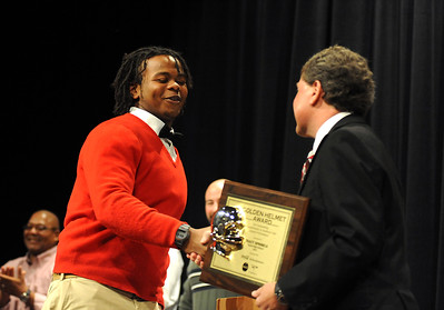 Tracy Sprinkle of Elyria football receives the Golden Helment Award from Gregory Finton of Elyria Coca Cola Refreshments at EHS Peforming Arts Center on Nov. 15.   Steve Manheim