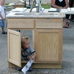 Peyton Ramsier, 18 months, of South Amherst plays peek-a-boo from underneath a vanity sink at the DPR Stone Counter Tops display that his mother overseas for the family business. His brother …