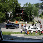 East Cleveland residents gather outside abandoned house to help search for more bodies Sunday, July 21, 2013, in East Cleveland, Ohio. Police Chief Ralph Spotts told volunteers checking vaca …