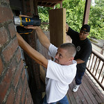 Al Harrison boards up a house Sunday, July 21, 2013 where a 35-year-old registered sex offender lived in East Cleveland, Ohio. The suspect, from East Cleveland, has indicated he might have b …