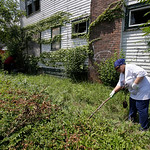 Fheila McCoy searches bushes outside a abandoned home Sunday, July 21, 2013, in East Cleveland, Ohio. Police Chief Ralph Spotts told volunteers checking vacant houses in a neighborhood where …