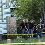 Law enforcement and FBI stand at the back of a boarded-up home where bodies were found earlier in the day Saturday, July 20, 2013 in East Cleveland, Ohio. Police say three bodies have been f …