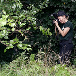 A woman from the Ohio Bureau of Criminal Identification and Investigation takes pictures in a wooded area Sunday, July 21, 2013 near where three bodies were recently found in East Cleveland, …