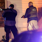 Police officers aim their weapons Friday, April 19, 2013, in Watertown, Mass. A tense night of police activity that left a university officer dead on campus just days after the Boston Marath …