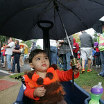 Dalton Colt Morcus, 1, of Lorain, sheilds himself from the raindrops shortly after he was judged on his costume at the 40th Annual Woolly Bear Festival in Vermilion.