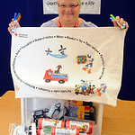 Linda Taylor,  a Red Cross volunteer from Lorain, and leader for the pillowcase project, holds a pillowcase above emergency preparedness items at the American Red Cross in Elyria on Aug. 12. …