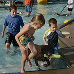 Paige Miller, 7, and brothers Caden, 11, and Cale, 5, of Amherst, walk with their chocolate lab Grady as he shakes off after a game of fetch on Aug. 26 during the Soggy Doggy Pool Party in O …