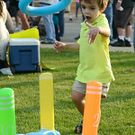 Liam Starett, 3, of Amherst plays with a ring toss set up at the annual dancing downtown event in Amherst on Aug. 2. KRISTIN BAUER | CHRONICLE