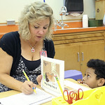Kindergarten teacher Karen Abfall talks to her new student, Coran Allen, as she does the kindergarten assessment testing to see how prepared he is for the new school year at Kindergarten Vil …