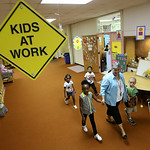 Kathy Petersen walks her kindergarten class back to their room at Kindergarten Village in Elyria. The students are in their first day at school and will be joined by more classmates this wee …