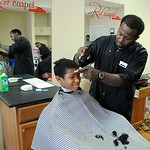 Dylan Bekely, 12, of Lorain, gets a hair cut by stylist Antwon President at Red Carpet Haircutting Salon, 914 Broadway in Lorain, on Aug. 18. The new shop gave free haircuts to returning sch …
