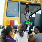 Lucy Acevedo, a parent volunteer, and Credit Recovery Academy students Makeisha Price, 16, and LaVonda Sims, 16, hand school supplies to Bre-Aja Tucker, 17, all of Lorain, to stuff the schoo …