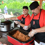 Tony Kitson and Mike Velez, both from the Elyria Salvation Army, serve up pulled pork and green beans in an attempt to win a trophy at the Soup Kitchen Cook-Off fundraiser on July 26. KRISTI …