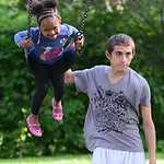 Christopher Hanlan, 15, pushes Shania Edwards, 3, both of Oberlin, on the swings at the playground on July 8.   KRISTIN BAUER | CHRONICLE