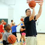 Elyria firefighter Mark Slack instructs Jeremiah Eldemire, 10, of Elyria, in free-throw shooting at the Reach and Rise Elyria Firefighters Basketball Camp at Elyria South Recreation Center o …