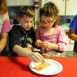 """Madeline Dean-Dielman and Robbie Castro, of Amherst, place candies on a graham cracker in an assembly line demonstration at the """"History Through Young Eyes"""" program at Amherst Sandstone Vill …"""