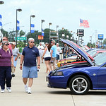 Spectators walk down a row Ford Mustangs on display during the annual Mustang and Ford Show at Nick Abraham's Ford in Elyria Sunday afternoon. ANNA NORRIS/CHRONICLE