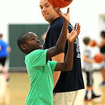 Elyria firefighter Mark Slack instructs Elisha Fisher, 10, of Elyria, in free-throw shooting at the Reach and Rise Elyria Firefighters Basketball Camp at Elyria South Recreation Center on Ju …