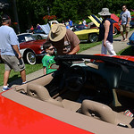 Aidan Miller, 6, of Wakeman, and his grandfather, Mike, of New London, look at many of the Corvettes at the Corvette show in Vermilion on July 12.  KRISTIN BAUER | CHRONICLE