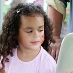 Marley McNeal, 5, of Elyria, checks out a kitty cat painted on her face during the Lorain County Historical Society's 15th annual Ice Cream Social fundraiser at The Hickories in Elyria Sunda …